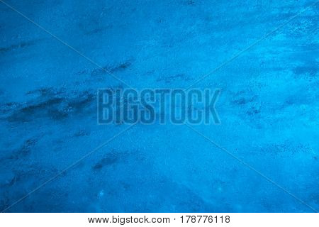 Detail of blue ice wall inside glacier tunnel illuminated by sunlight
