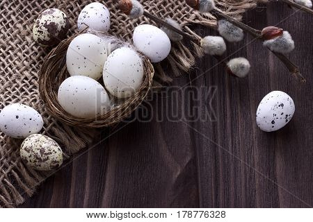 Easter Eggs In The Nest On Burlap Cloth With Pussy Willow Branches.