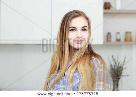Young beautiful girl in a blue checkered shirt and blue jeans stands in the kitchen. Home interior.