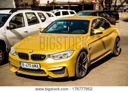 BUCHAREST ROMANIA - APR 1 2016: Luxury yellow BMW m4 sport coupe convertible parked on the streets of eastern european capital Bucharest