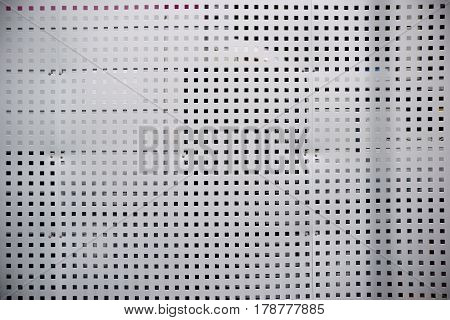 A sheet metal grid with square holes for separation privacy and visual protection.