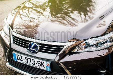 PARIS FRANCE- FEB 12 2017: Detail of the front part of a Lexus ct200h limouse - xenon led lights and the iconic Lexus logotype. Lexus CT 200h is a hybrid electric automobile introduced by Lexus as a premium sport compact hatchback.