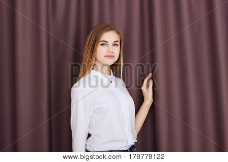 Office Girl in white blouse against a background of brown curtains