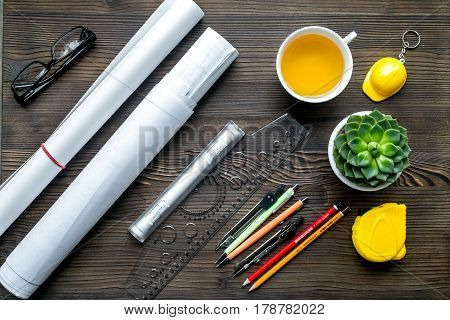 Architects workplace with constructor tools with cup of tea and glasses on wooden table background top view