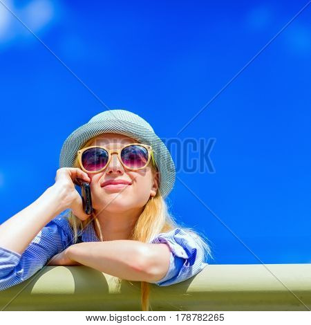 Happy Hipster Girl Talking Mobile Phone On City Street