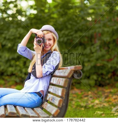 Young Hipster Taking Photo With Retro Photo Camera Sitting On Bench In The Park