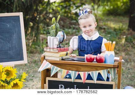 Portrait Of A Beautiful Young First-grader Sitting At A Desk