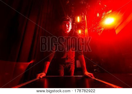 Roadie rolling a flightcase on stage, brightly lit by a red stage light.