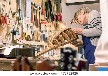 Luthier inspecting his halfway finished lute, standing behind his work bench, surrounded by the tools of the trade of a craftsman.
