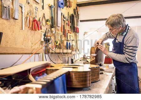 Luthier - instrument maker - applying masking tape to an old acoustic guitar body with another guitar in the foreground