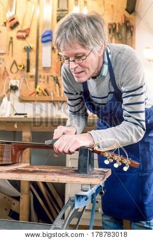 Guitar repairer filing the frets of an acoustic guitar on a workbench