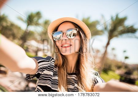 Smile Woman In Hat And Sunglasses Taking Selfie With Mobile Phone From Hands On Summer Resort Palms