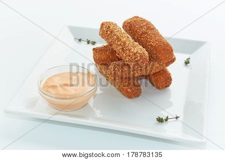 Breaded fried cheese sticks with sauce. White plate.