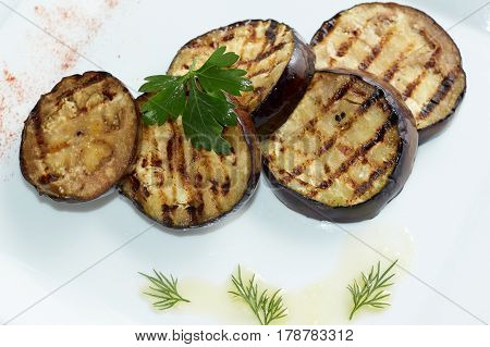 Grilled eggplants decorated with green leaf. Top view. White plate.