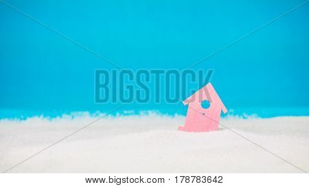 Symbol of little red house on the sand with bright blue background.