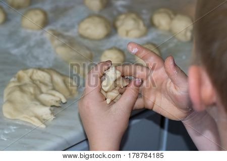 Child hands handling doug for cookies with lots of flour