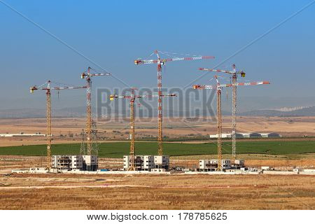 View of cranes on construction site of new neighborhood in Kiryat Gat, Israel.