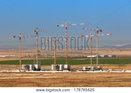 View of cranes on construction site of new neighborhood in Kiryat Gat, Israel.