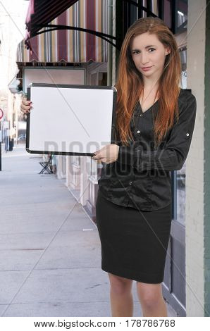 Beautiful young woman holding up a blank dry erase sign