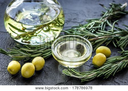 jar with natural oil with fresh olives and rosemary on stone table background