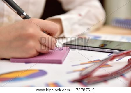 Businesswoman Writes Data On Sticker