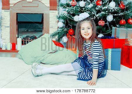 Little girl in blue striped dress and a white bow on her head.She sits around the Christmas tree and the fireplace.Creative toning of a photograph.