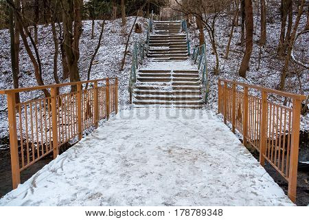 Old abandoned park in winter. Staircase and bridge covered with snow
