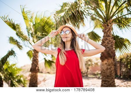 Cheerful Lovely Young Woman In Red Dress And Hat Walking And Talking On Mobile Phone On Summer Resor