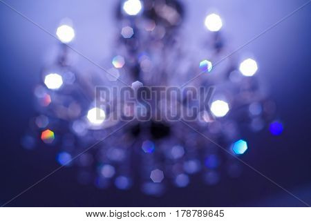 Close up of crystal glass chandelier hanging from ceiling blurred background