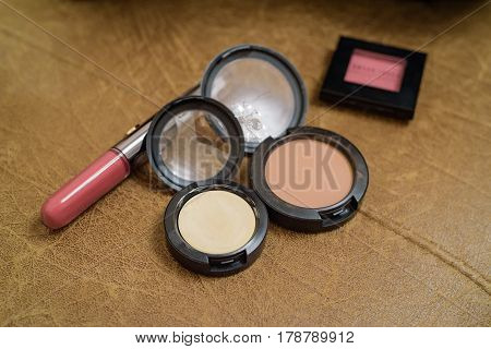Close up of lipstick, concealer, powder and blush lying on brown background