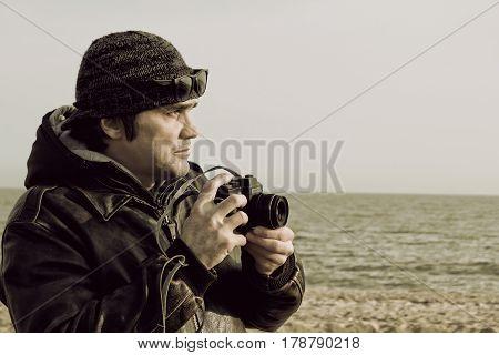 Photographer with retro photo camera on sea beach.Retro style toned image.