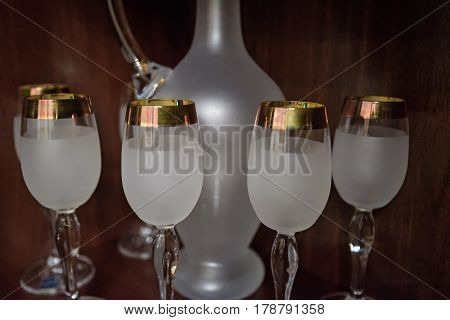 Closeup of set of crystal wineglasses and jug in wooden cabinet