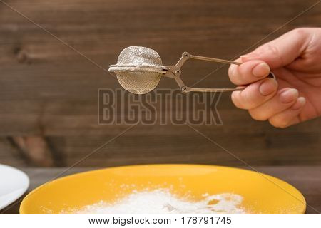 Closeup of hand holding tea siever with flour in it