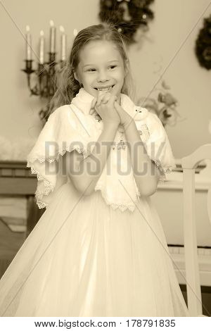 Cute little girl in smart white dress Christmas around the fireplace which burn holiday candles.Black-and-white photo. Retro style.