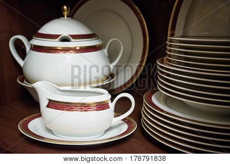 Closeup of white decorated china teaset and piled plates on wooden shelf
