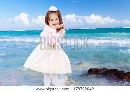 Dressy little girl long blonde hair, beautiful pink dress and a rose in her hair.She holds the palm of your hand near their cheeks.White sand , blue sea and blue sky with clouds.