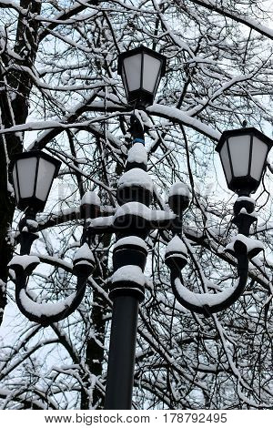 Close up on old orante street lamp during snow storm