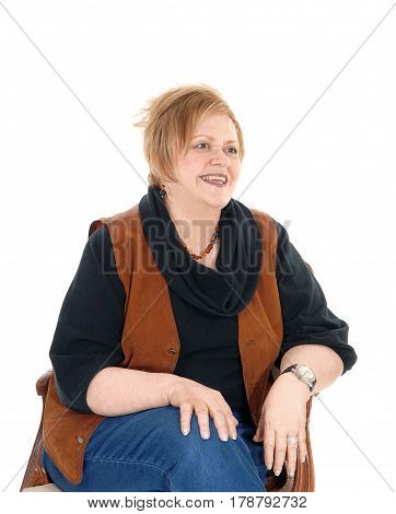 A lovely senior citizen woman in a brown vest sitting in an old armchair relaxing isolated for white background.