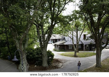 Plimoth Plantation, Plymouth, Massachusetts - September 10, 2014 - Wide view of one of the utility cottages at the Welcome Center at Plimoth Plantation with pathways trees and foliage and a single worker checking her phone on a bright sunny day in Septemb