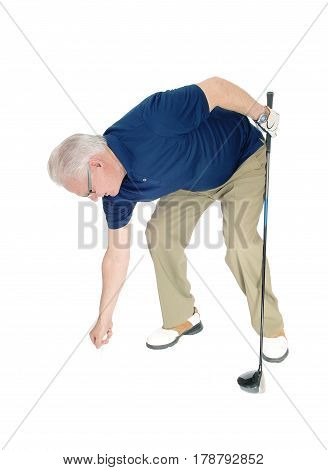 A seventy old senior standing with his blue t-shirt holding his iron in his hand and pleasing the golf ball isolated for white background.