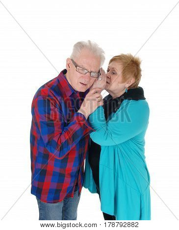 A older senior couple standing isolated for white background and the wife is whispering in his ear some gossip.