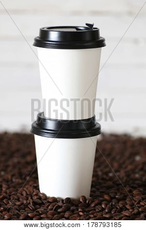 coffe in a white paper cup and beans on a table