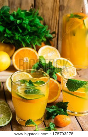 Refreshing citrus lemonade with fresh mint glasses bottle cut fruits on wood kitchen table by window summer