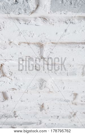 Abstract vertical white background of a shabby brick wall.