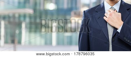 Detail of a businessman adjusting his necktie