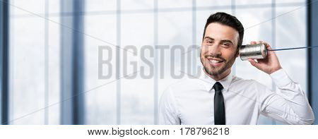 Smiling man talking on a thin can