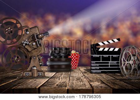 Cinema concept of vintage film reels, clapperboard and projector ond old wooden background.