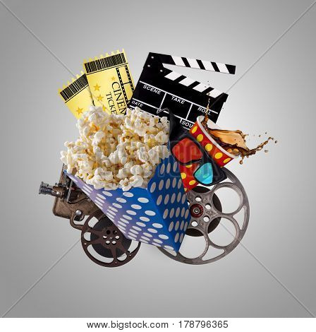 Pop-corn, movie tickets, clapperboard and other things in motion. Cinema concept.