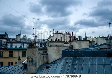 Detail of typical Paris rooftops during a cloudy afternoon of autumn in France picture of a few traditional Parisian roof tops on Haussmann style buildings shortly before a rainstorm