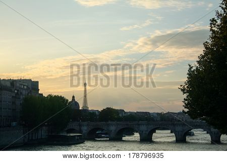 Typical view of Paris with Pont-Neuf and Seine river at sunset. Eiffel Tower can be seen in the background